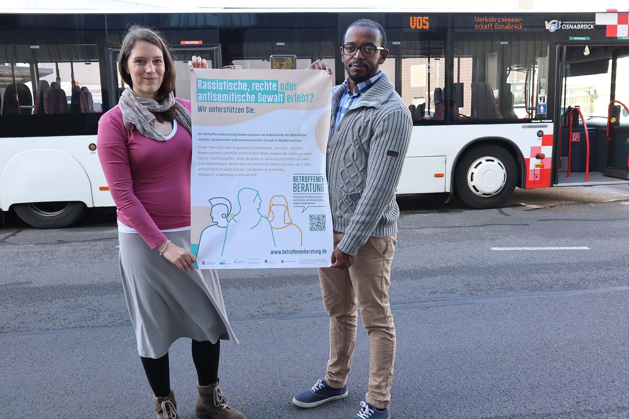 Sara Josef und Ambachew Anjulo von Exil präsentieren das Plakat der Betroffenenberatung Niedersachsen vor einem Bus der Stadtwerke Osnabrück